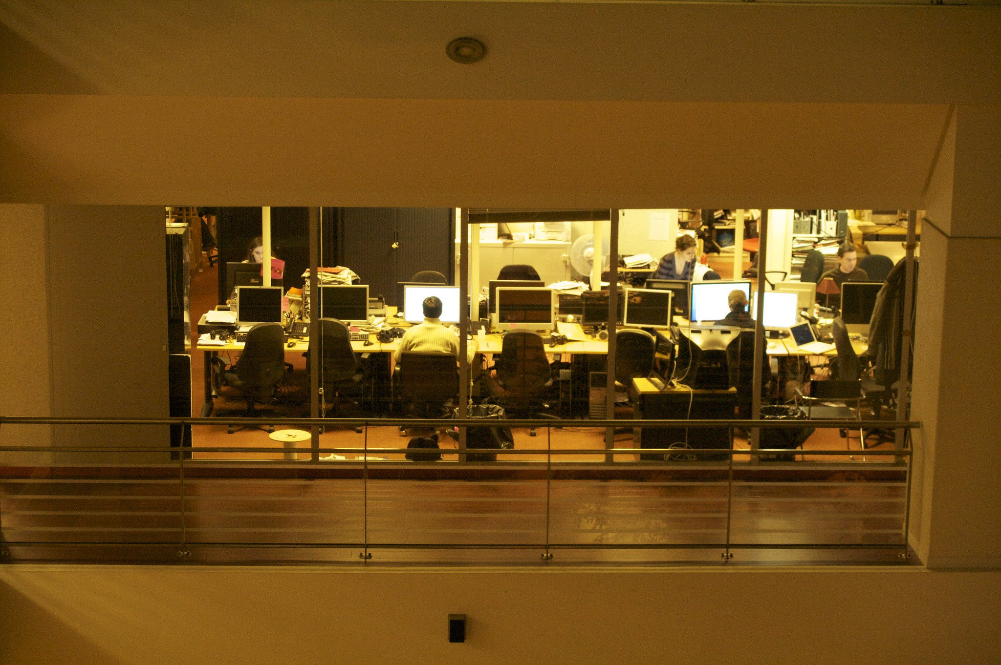 A photo peering into a window of the French newsroom, Le Point, where reporters are working at their desks.