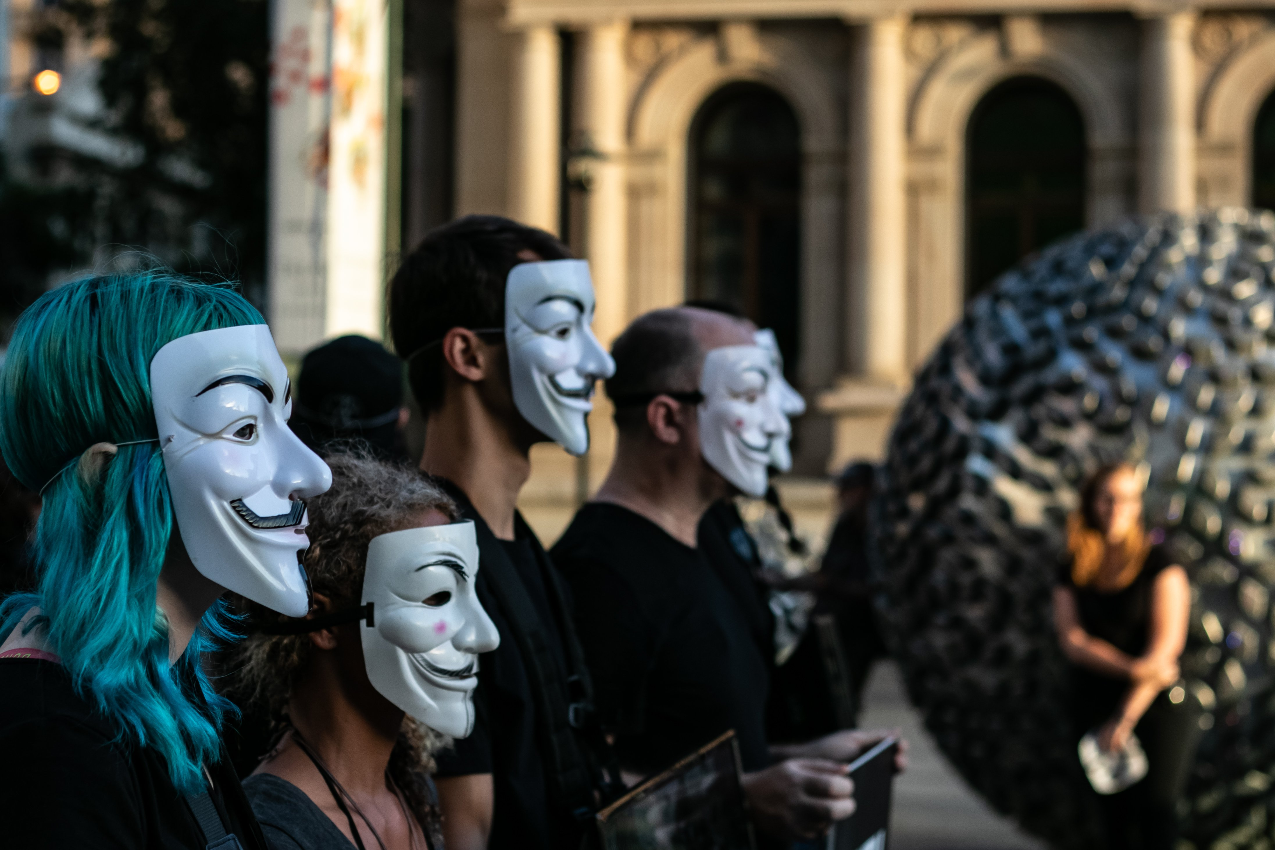 A crowd in a protest wearing Guy Fawkes masks.