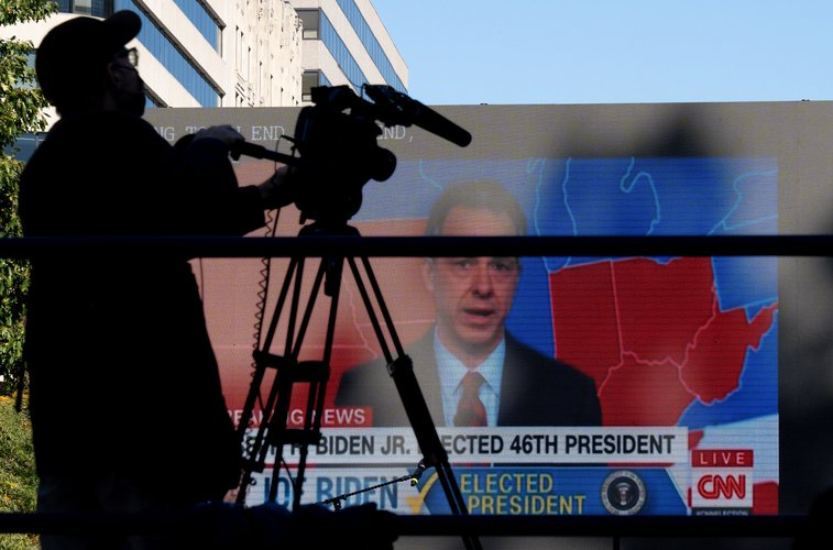 A shadow of a camera man against the background of a large television, showing the projected electoral map of the United States on CNN with Jake Tapper.