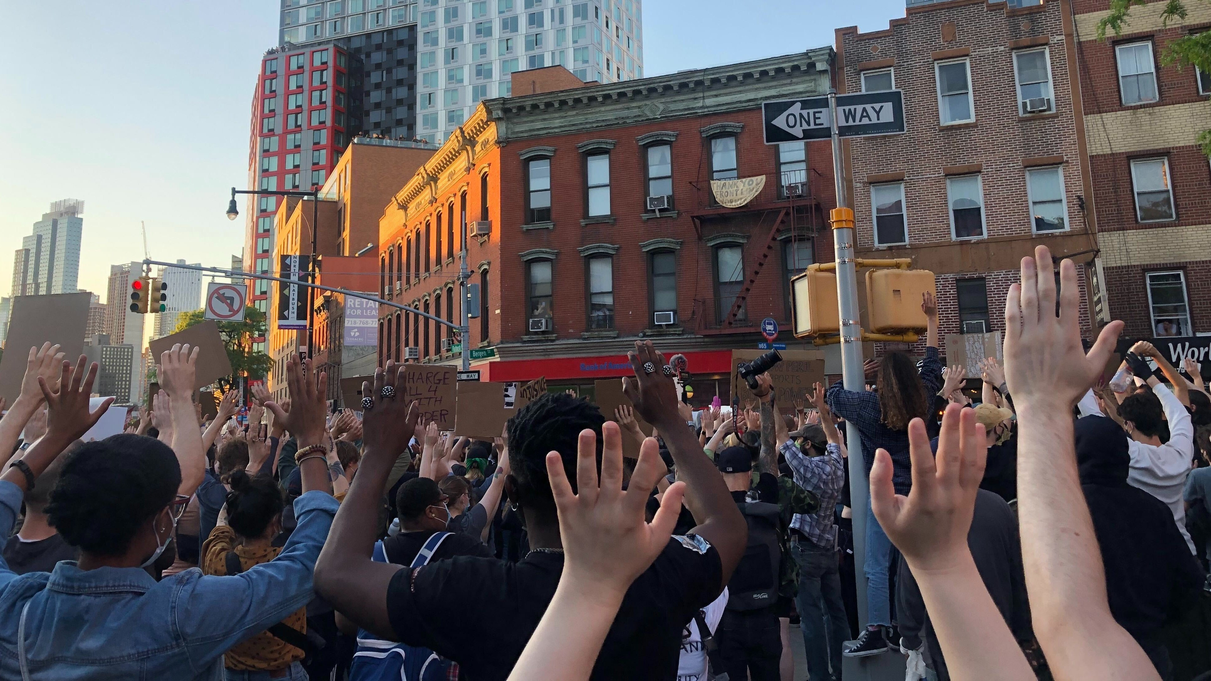 Protestors at a George Floyd action in Brooklyn raise their hands