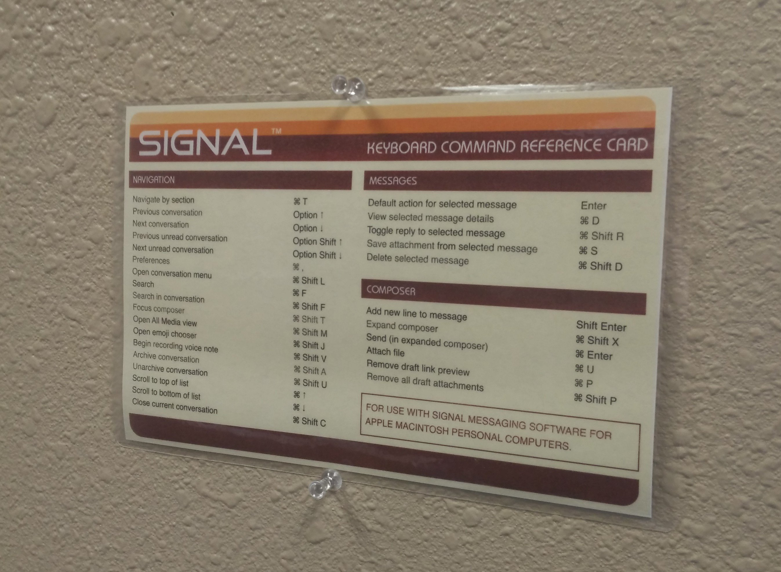 "A Signal ""reference card"" with shortcut commands, pinned to the wall."