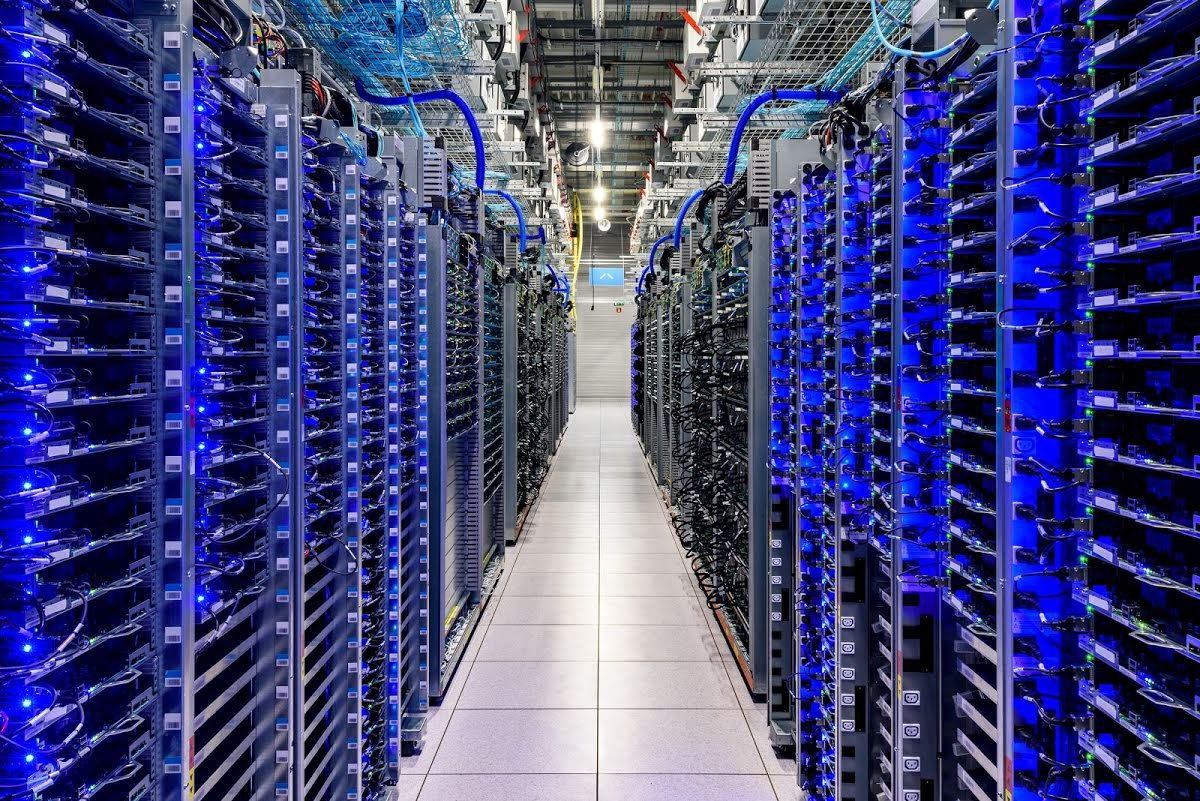 Rows of server racks, glowing blue inside of a Google data center.