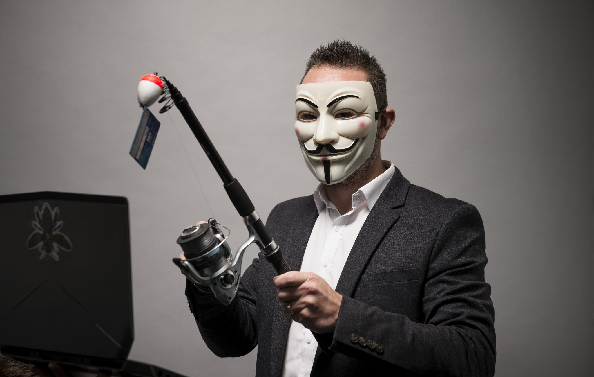 Photo of a man in a Guy Fawkes mask, with a fishing reel in hand.