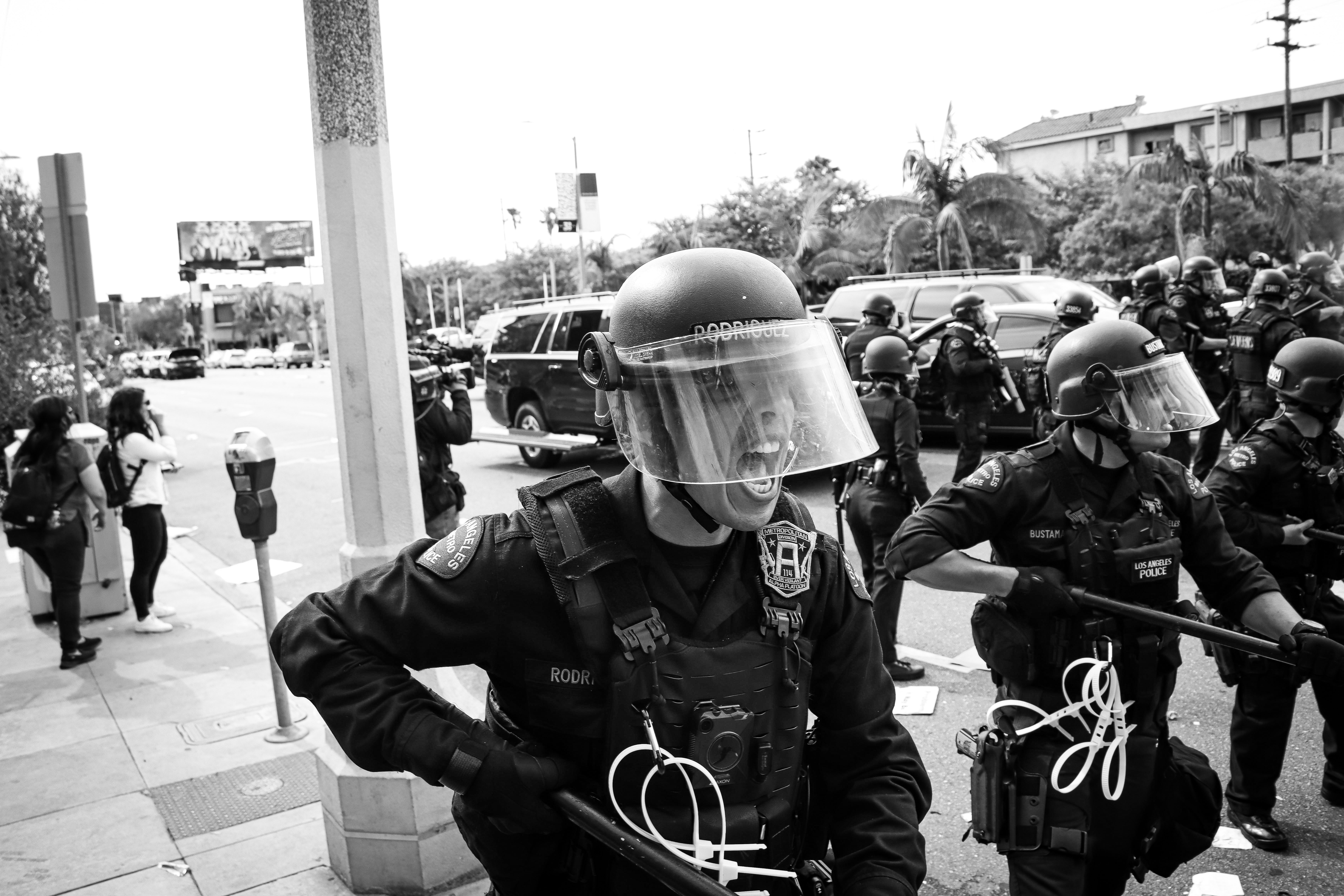 Los Angeles police officer pushing back protesting crowds