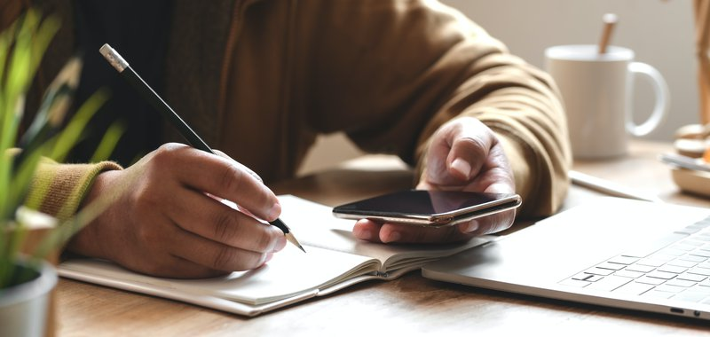 Cover image of a person holding a smartphone while writing