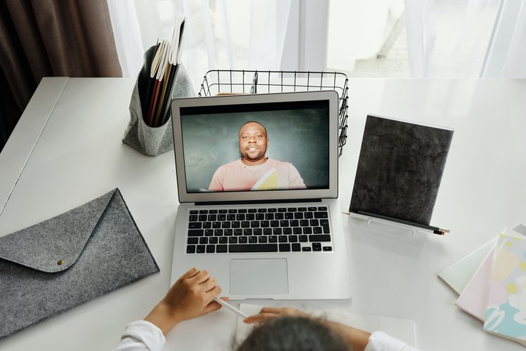 An image of a girl on a video call on her laptop. The screen displays an imgae of the person she's speaking to.