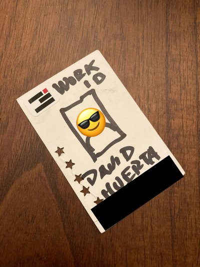 Example of an redacted work ID card which is actually a sharpie illustration it has a sunglasses face emoji over the face and black rectangle over the ID number